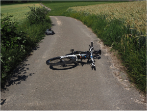 bike laying on road with book back off to the side