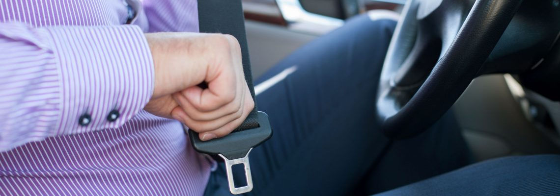 man buckling seat belt while in driver's seat